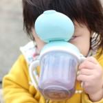 マグで水分補給する子ども