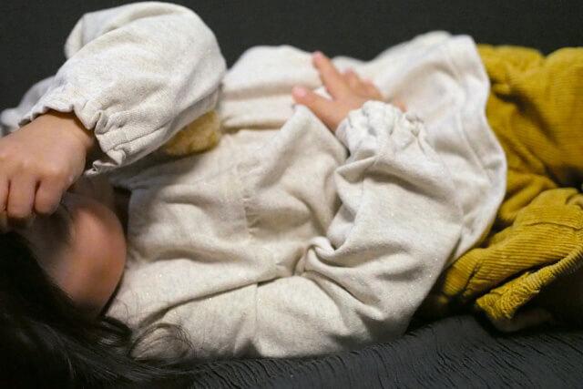 横になって泣いている子ども