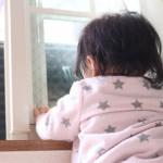 窓の外を見つめる赤ちゃん