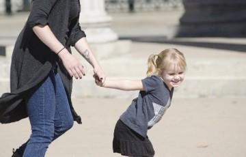 ママの手を引っ張る外国の女の子