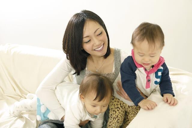 双子の赤ちゃんたちと遊ぶママ
