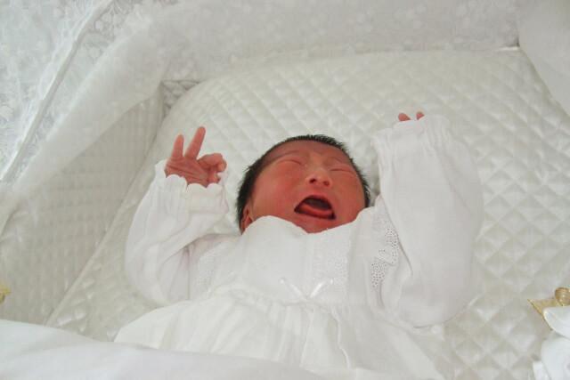 ベビーベッドで泣いている赤ちゃん