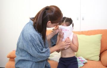 女の子の着替えを手伝うママ