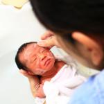 出産後にきれいにしてもらう小さな赤ちゃん