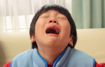 上を向いて泣く男の子