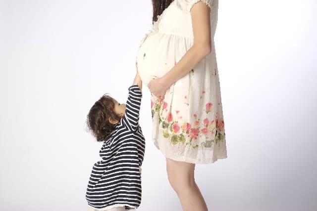 妊娠したママのお腹を触る女の子