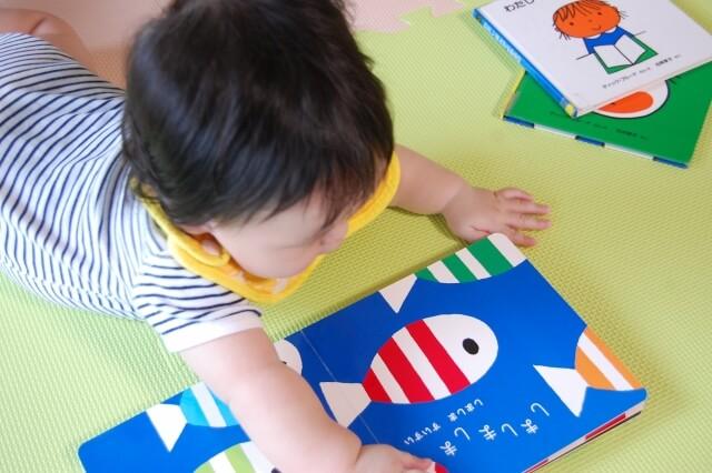 ひとりで絵本を読む赤ちゃん
