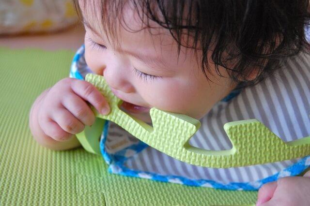 フロアーマットを咥える赤ちゃん
