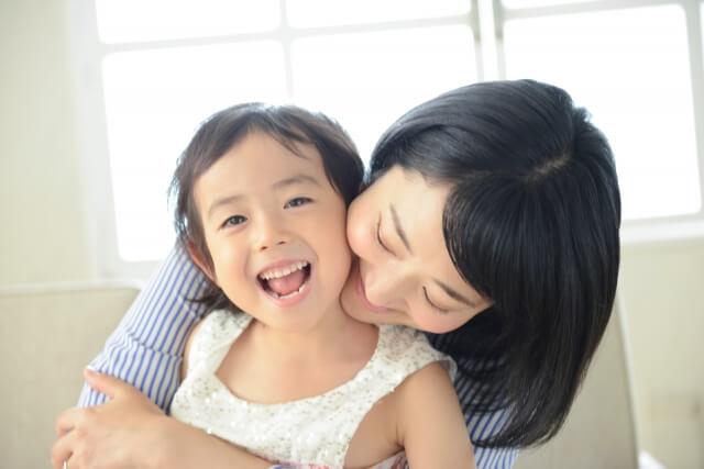 ママに後ろから抱っこされる女の子