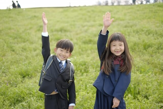手を挙げる小学生の男の子・女の子