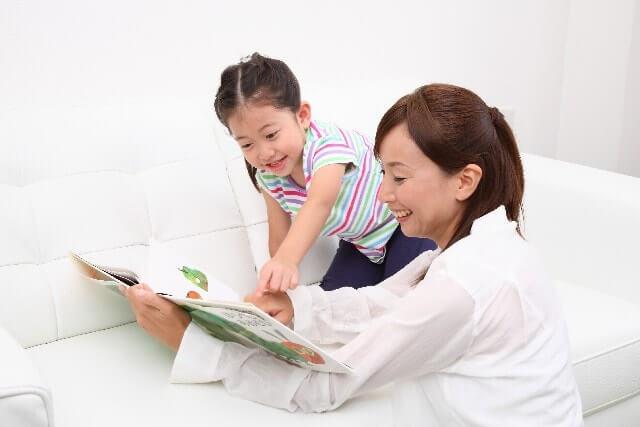 女の子に絵本を読むママ